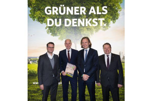 Vier Männer vor einer Werbung von Zukunft Erdgas.