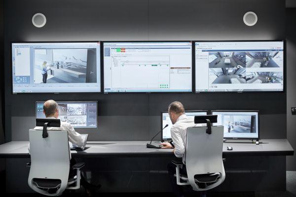 Zwei Männer überwachen mit verschiedenen Bildschirmen ein Gebäude.