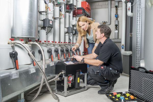 Ein Handwerker zeigt in einem Heizraum einer Frau, wie die Heizungswasseraufbereitung mit