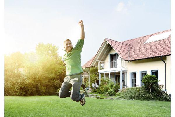 Ein Mann springt vor einem Haus in die Luft.