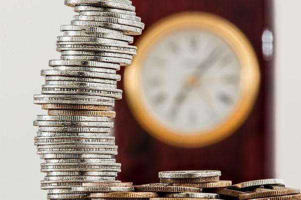 Ein Stapel Gold- und Silbermünzen vor einer Uhr.