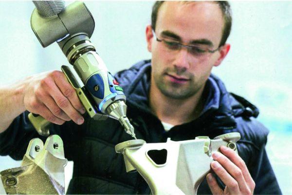 Ein Mann bearbeitet etwas mit einem Druckluftwerkzeug.