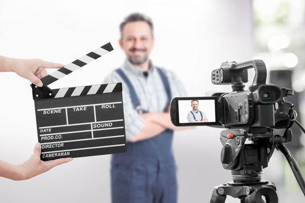 Ein Handwerker wird von einer Kamera gefilmt, jemand hält dabei eine Klappe vor ihn.