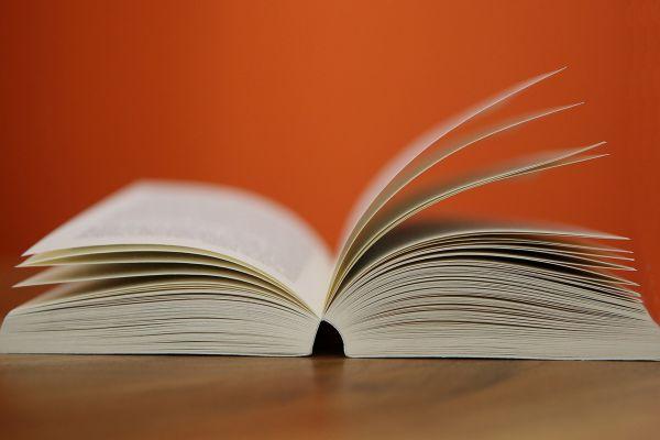 Ein aufgeschlagenes Buch auf einem Tisch.