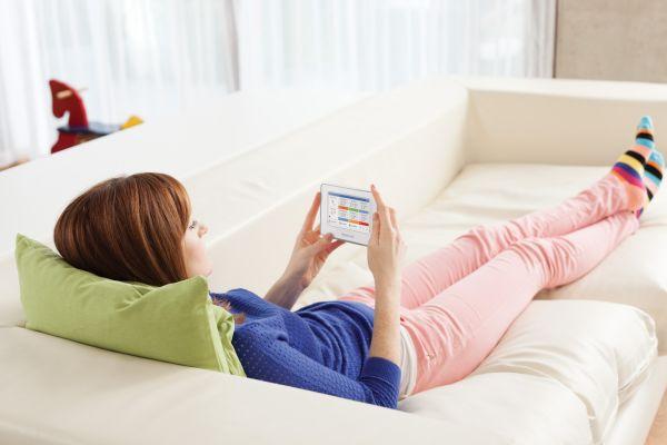 Eine Frau liegt mit einem Smartphone auf dem Sofa.