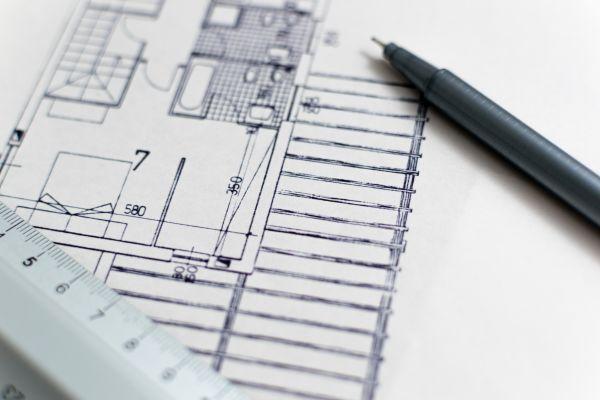 Plan einer Wohnung auf einem Tisch neben einem Lineal.