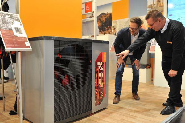 Jörg Schickedanz von Nibe Systemtechnik informiert einen Besucher über die Luft/Wasser-Wärmepumpen der Serie F2120.