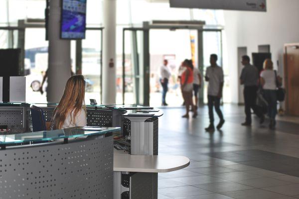 Eine Frau sitzt an einem Empfangstresen, davor gehen Leute vorbei.