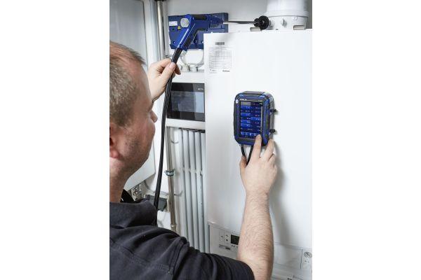 Kundendienstmonteur Christian Michel von der Profi-Wärme-Service GmbH führt eine Abgasmessung an einer Gas-Brennwertheizung durch.