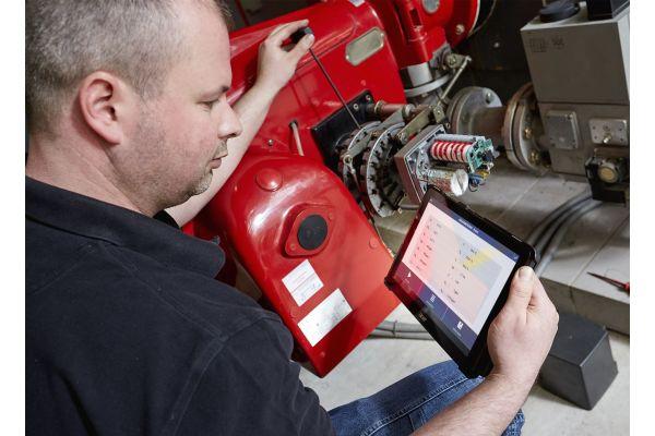 Kundendienstmonteur Christian Michel von der Profi-Wärme-Service GmbH sieht sich  die Messdaten eines Brenners per App auf seinem mobilen Endgerät an, während er die Einstellungen vornimmt.