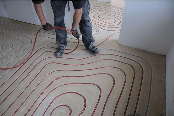 Ein Handwerker beim Verlegen der Heizrohre einer Fußbodenheizung.