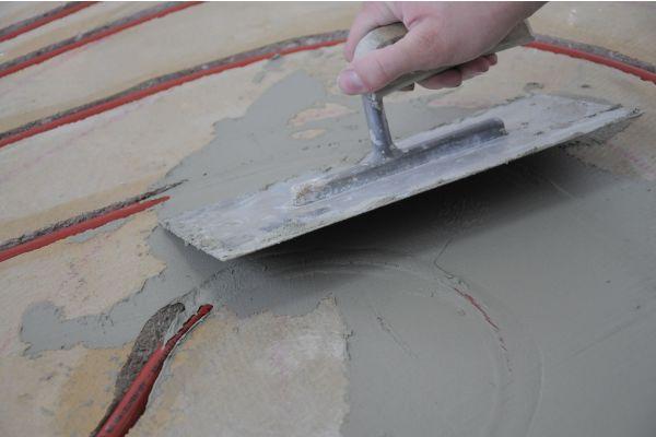 Ein Handwerker verspachtelt die Kanäle des Heizungsrohrs einer Fußbodenheizung.