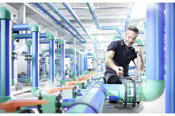 Ein Installateur baut ein Kunststoff-Rohrleitungssystem von aquatherm ein.
