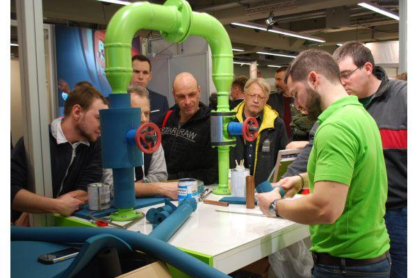 Eine Gruppe Männer sieht einem Handwerker zu.