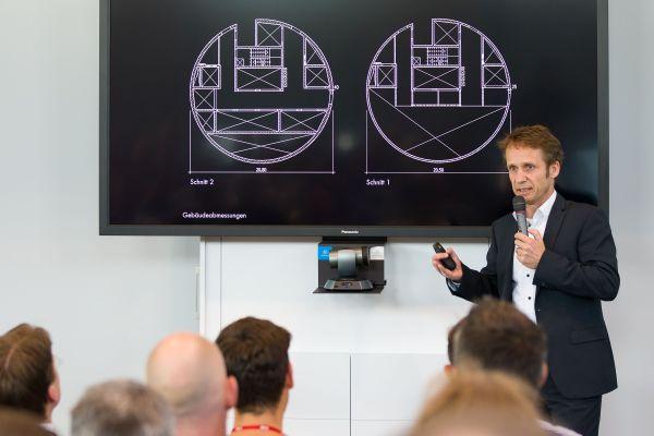 Ein Mann steht vor einem Bildschirm mit Grundrissen.