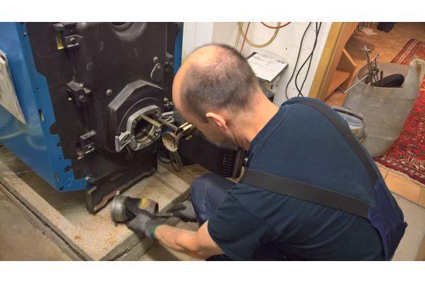 Ein Handwerker reinigt den Brenner eines Ölkessels.