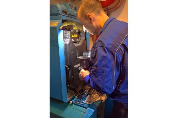 Ein Handwerker arbeitet an einem Ölheizkessel.