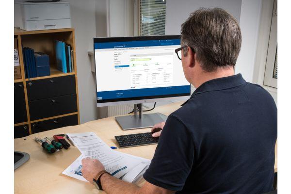 Ein Mann sitzt vor einem Computerbildschirm.
