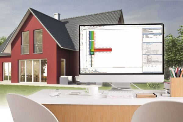 Ein Computerbildschirm auf einem Schreibtisch, im Hintergrund ein Haus.
