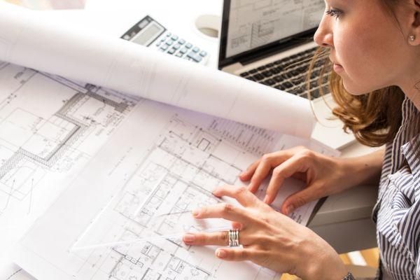Eine Frau betrachtet Baupläne.
