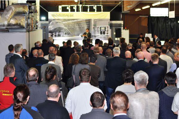 Ein Mann hält vor Publikum eine Rede.