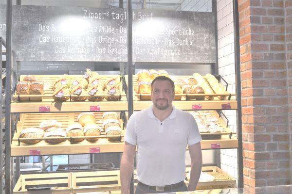 Ein Mann steht hinter einem Verkaufstresen einer Bäckerei.