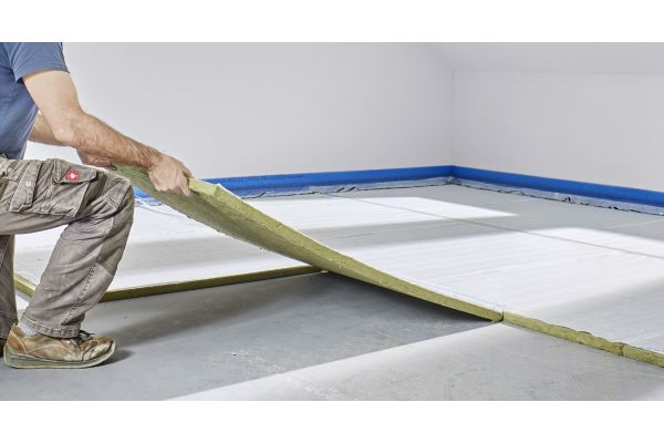 Ein Handwerker verlegt Verlegeplatten für Fußbodenheizungs-Klettsysteme.