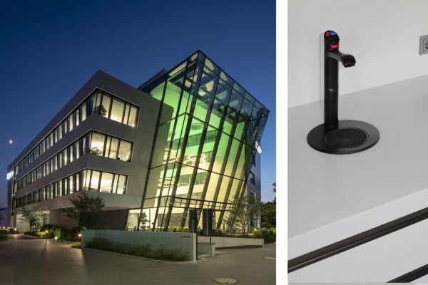Das Bild zeigt die Außenansicht des Gebäudes und die schwarze Zip-Armatur von Clage.
