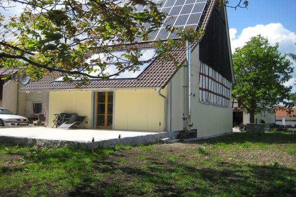 Ein Bauernhaus mit Photovoltaik-Anlage von außen.