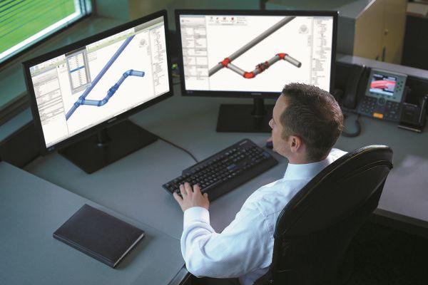 Ein Mann arbeitet vor zwei Computerbildschirmen.