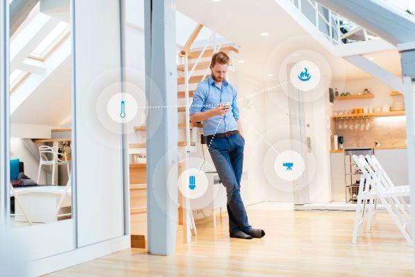 Ein Mann steht an ein Treppengeländer gelehnt in einem Haus und schaut auf sein Smartphone, um ihn herum sind verschiedenen Symbole.