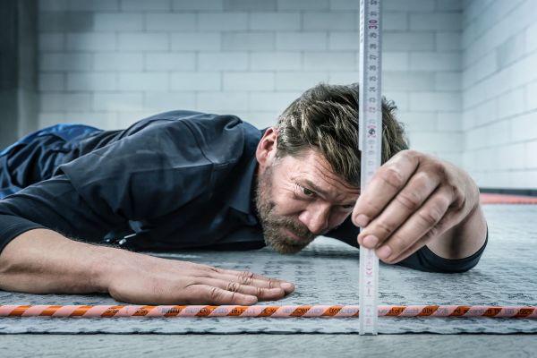 Ein Handwerker misst die Höhe des Fußbodenheizungs-Klettsystem