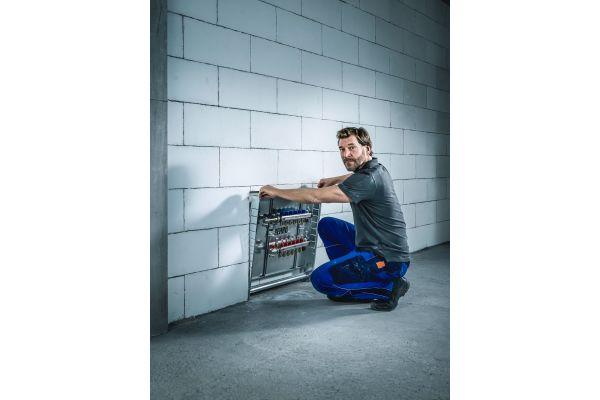 Ein Handwerker installiert einen Fußbodenheizungsverteiler von Rehau.