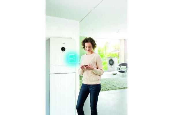 Eine Frau steht mit einem Smartphone vor einer Wärmepumpe.
