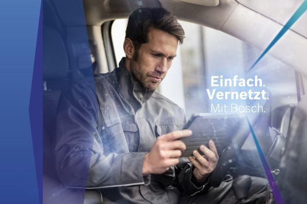 Ein Handwerker betrachtet in einem Auto ein Tablet.
