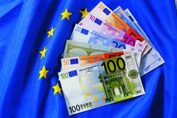 Das Bild zeigt Geld auf einer EU-Flagge.