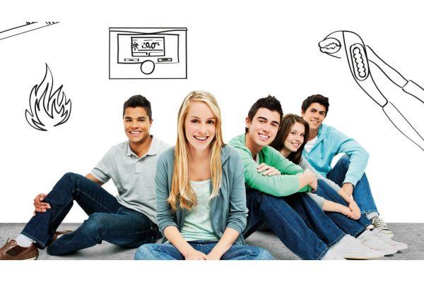 Fünf Jugendliche sitzen auf dem Boden, daneben ein