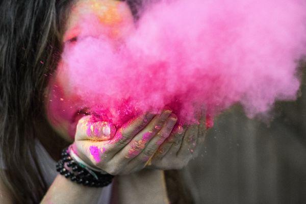 Eine Frau bläst rosa Pulver aus ihren Händen.