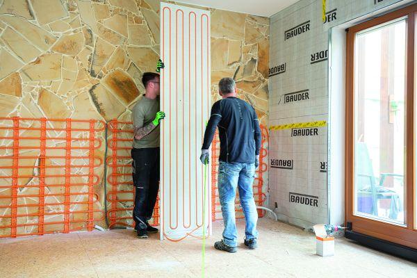 Zwei Handwerker beim Einbau von Wand-Modulen für eine Trockenbau-Wandheizung/Kühlung.