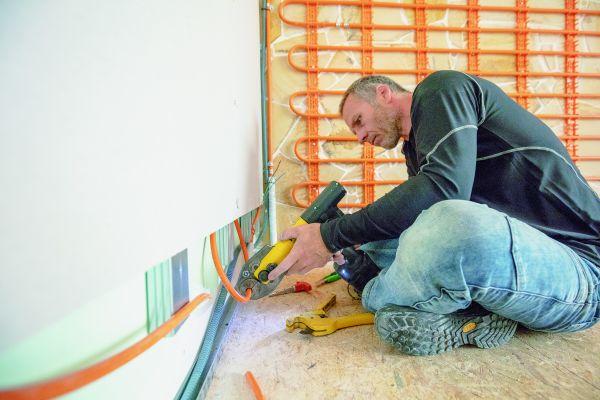 Ein Handwerker beim Einbau von Wand-Modulen für eine Trockenbau-Wandheizung/Kühlung.