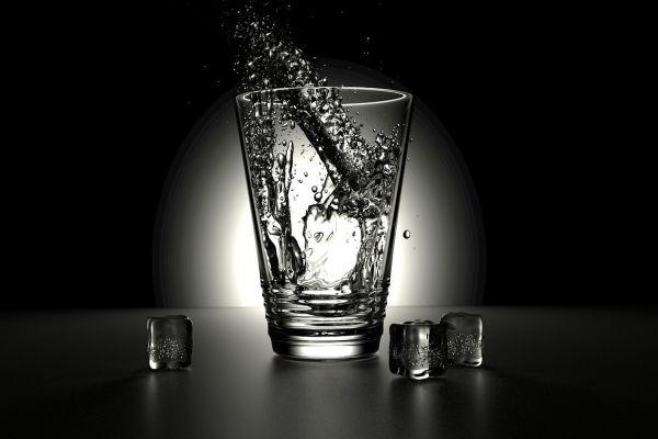 Ein Glas Wasser auf einem Tisch, daneben Eiswürfel.