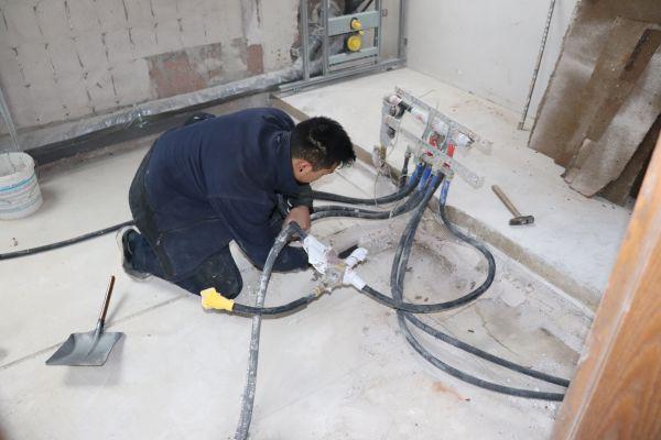 Ein Handwerker entfernt alte Wasserleitungen.