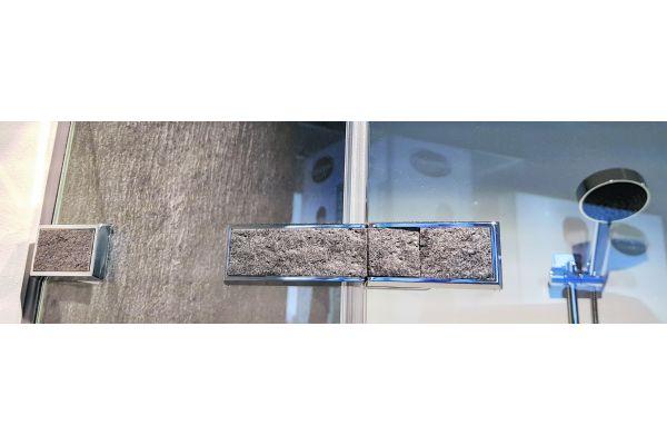 Es sind die Details, die bei Duscholux den entscheidenden Unterschied machen; wie diese Beschläge, die im gleichen Echtstein-Design ausgeführt sind wie die Wandpaneele.