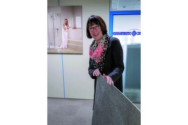 Duscholux-Geschäftsführerin Petra Meier mit einer der Innovationen, mit denen sich die Duschmarke vom Wettbewerb absetzt: `PanElle Stone´ – ein Dusch-Wandpaneel mit feinst geschnittener Echtstein-Beschichtung.