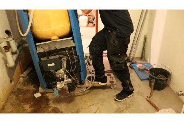 Ein Handwerker hebt einen Heizkessel auf ein Rollbrett.