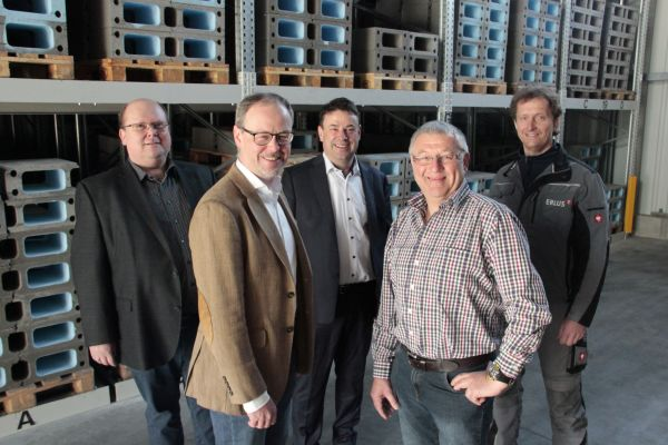 Fünf Männer stehen nebeneinander vor einer Baustelle.