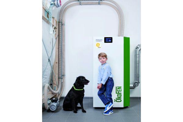 Ein Junge und ein Hund vor einem Pelletkessel.