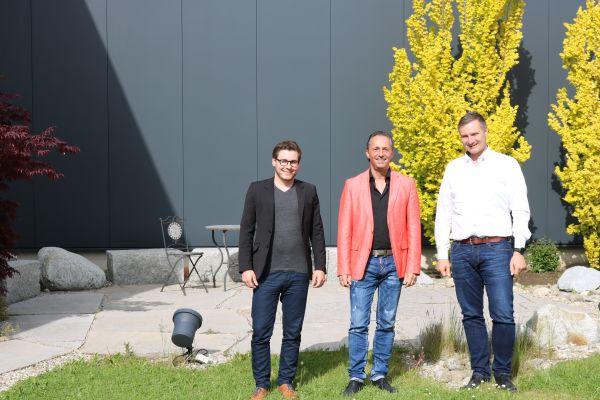 Drei Männer stehen vor einem Gebäude.