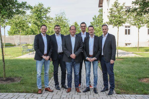 Sechs Männer stehen in einem Garten.
