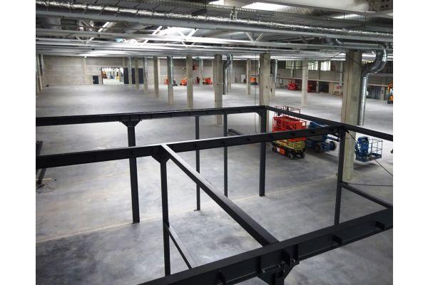 """Blick in eine von drei """"digitalen"""" Fabrikationshallen mit je 11.000 m2. Im Vordergrund das Gerüst einer künftigen """"Meisterbude""""."""